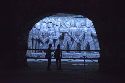 Blick durch einen Tunnel auf eine großformatige, aus Stein gehauene Figurengruppe, die von bläulichem Licht erhellt wird.
