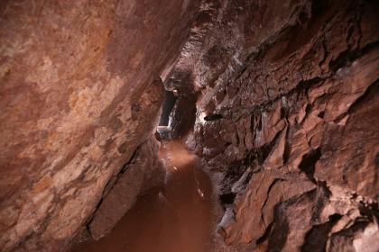 Blick in das Innere eines Bergwerkes. Gezeigt wird hier ein enger, Wasser führender Stollen mit rötlich braunen, schräg nach rechts geneigten zerklüfteten Wänden.