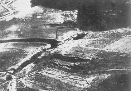 Schwarzweiß-Aufnahme eines Schrägluftbildes, welches eine Hangrutschung zeigt.