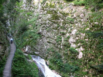 Rechts eine Felswand, die stellenweise von Gräsern und Sträuchern überwachsen ist. In der Mitte fließt ein steiler Fluss. Am linken Hang befindet sich eine lange Treppe.