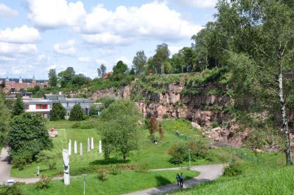 Das Foto zeigt rechts und hinten eine teilweise überwucherte Steinbruchwand. Die Kuppe des Gesteins ist mit Bäumen bestanden. Vor der Wand liegt eine Grünanlage mit Bäumen und Spazierwegen. Links hinten sind Stadthäuser zu sehen.