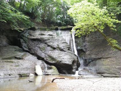 Blick auf steile graue Felswände, die links schräg aufeinanderliegen. Rechts fließt ein dünner Wasserfall zwischen den Felsen und bildet unten einen nach links führenden Bach mit steinigem Ufer.