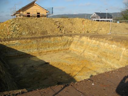 Das Bild zeigt eine rechteckige Grube, in der geschichtet Gestein in unterschiedlichen Brauntönen ansteht. Dahinter befinden sich zwei Häuser, von denen eins mit einem Baugerüst verkleidet ist.