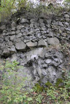 Das Foto zeigt einen Felsen und in waagrechten Reihen daraufgesetzte, unregelmäßig geformte graue Steine, die zusammen eine Mauer bilden. Die bröckelig wirkende Mauer wird von Büschen und Sträuchern eingerahmt.