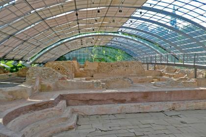 Blick auf die Überreste eines antiken römischen Bades. Im Vordergrund der Einstiegsbereich mit Treppenaufgang links, dahinter gemauerte Einfassungen und Ziegelsteinwände. Geschützt werden die Ruinen von einem halbkreisförmigen Gitterdach aus Metall.
