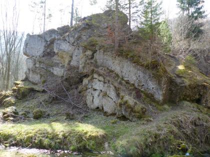 Das Bild zeigt mehrere auf einem Plateau übereinandergeschichtete Felsstücke. Nischen zwischen den Felsen sind mit Erde gefüllt oder bemoost. Auch dünne Bäume wachsen auf den Felsen. Am unteren Bildrand ist ein Wasserlauf zu sehen.