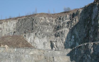 Blick auf eine nach rechts ansteigende Steinbruchwand mit hellgrauem, waagrecht abgestuftem Gestein. Links oben und darunter sind dunklere sowie bräunliche Bereiche zu sehen. Rechts macht die Wand einen Knick und liegt im Schatten.