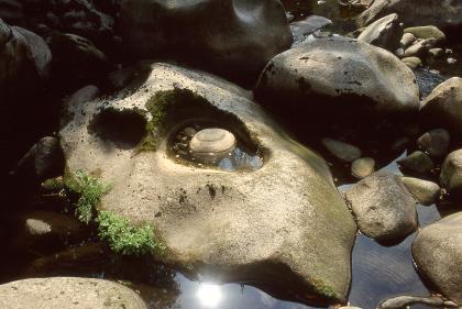 Das Bild zeigt einen bräunlichen Felsblock, der von Wasser und anderen Felsen umgeben ist. In der Mitte des Felsens ist eine mit Wasser gefüllte Vertiefung, in der wie eine Pupille ein kleinerer Stein schwimmt.