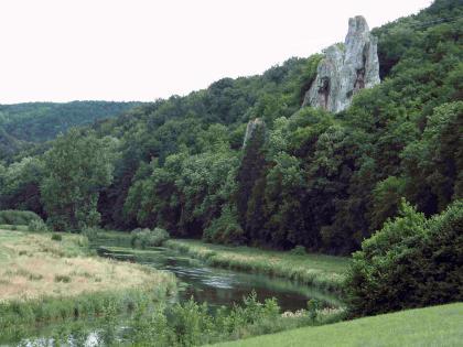 Ein von links hinten kommender Fluss knickt nach links vorne ab. Das Ufer links des Knicks besteht aus Schilf, das Ufer rechts aus einer schmalen Wiese. Gleich dahinter steigt ein bewaldeter Berg auf, aus dem rechts oben graue Felsnadeln hervorstehen.