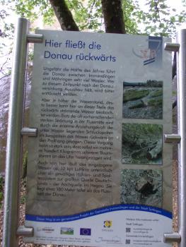 """Blick auf eine bebilderte, von Metallstangen gehaltene Schautafel mit dem Thema """"Hier fließt die Donau rückwärts""""."""