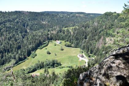 Blick über einen Felsenkopf rechts vorne auf eine kleine, von wenigen Häusern bestandene und nach links abfallende grüne Hochfläche, die auf drei Seiten von bewaldeten, teils steilen Berghängen umschlossen ist.
