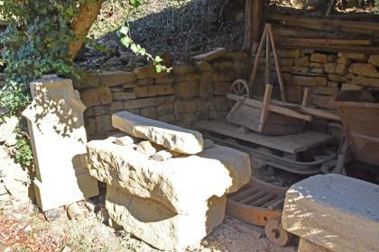In einem mit Steinmauern eingefassten, vorne offenen Unterstand sind ein Bildstock, mehrere grob behauene Gesteinsblöcke, eine Lore und ein Schubkarren abgestellt.