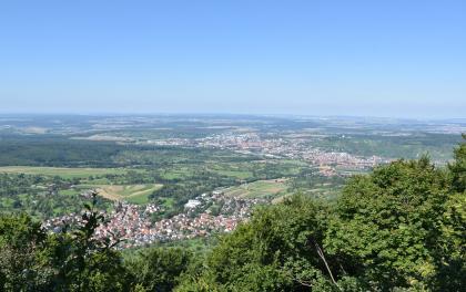 Blick von erhöhtem Standort auf eine weite, flachwellige Landschaft mit Feldern, Waldstücken und zahlreichen Ortschaften.
