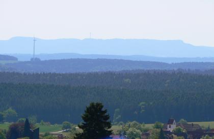 Blick von erhöhtem Standort über Baumspitzen und ein Kirchendach auf ausgedehnte, hintereinander gestaffelte Waldstreifen. Im Hintergrund ist der Umriss einer flachen, bewaldeten Anhöhe zu erkennen.