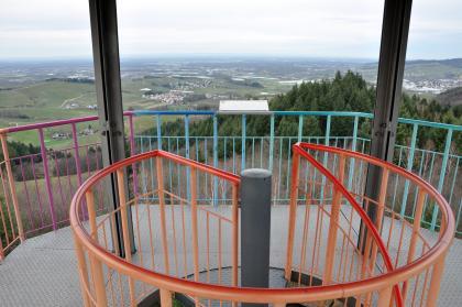 Das Foto zeigt eine Aussichtsplattform mit mehrfarbiger Brüstung aus metallenen Streben. Im Vordergrund der runde Handlauf des Treppenaufgangs. Im Hintergrund eine weite Landschaft mit Wäldern und Weinbergen.
