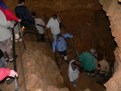 Blick von oben auf mehrere Höhlenbesucher, die über steile Metalltreppen in tief unten gelegene Höhlenbereiche absteigen.