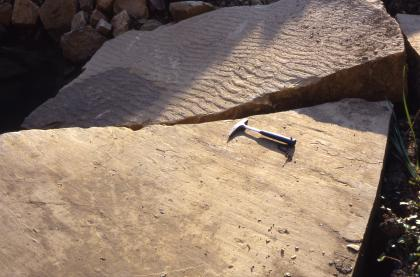Zwei Steinplatten aus hellbraunem bis rötlichem Gestein sind zu sehen. Die vordere Platte zeigt eine glatte Oberfläche, auf ihr liegt ein Hammer. Die hintere Platte hat eine wellig-gerippte Oberfläche.