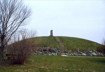Auf dem Bild ist ein mit Gras bewachsener Grabhügel zu sehen. Auf den Hügel hinauf führt eine Steintreppe, oben steht ein Monument. Im linken Vordergrund befindet sich ein kahler Baum