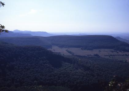 Blick von erhöhtem Standort über mehrere, hintereinander aufgereihte bewaldete Höhenrücken in bläulichen Farben.