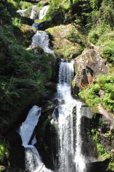 Schönes Bild eines mehrstufigen, über große Felsblöcke stürzenden Wasserfalles. Links gibt Wald Schatten, rechts ist ein steiler, bewachsener Hang erkennbar.