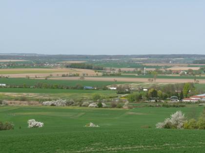 Hinter einer grünen Ebene im Vordergrund öffnet sich eine weite, leicht wellige Landschaft. Hier wechseln sich Grünland- mit Ackerflächen ab. Zu sehen sind auch weiß blühende Bäume, eine Bahnlinie, eine Autobahn und mehrere Ortschaften.