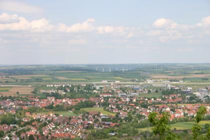 Blick aus großer Höhe über eine weite Landschaft mit einer Siedlung im Vordergrund. Zum Hintergrund hin sind Felder, Wiesen und bewaldete Hügel zu erkennen. Zwei dieser Hügel bilden ein Tal, das von einer langen, hohen Brücke überspannt wird.