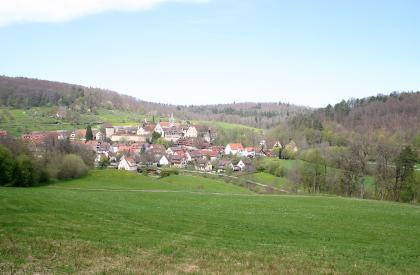 Etwas abgesenkt, hinter einer Grünfläche im Vordergrund, liegt eine kleinere, oval angeordnete Siedlung mit Stadtmauer und Türmen. Eingefasst wird der Ort von grünen Hügeln sowie umlaufenden Wäldern.