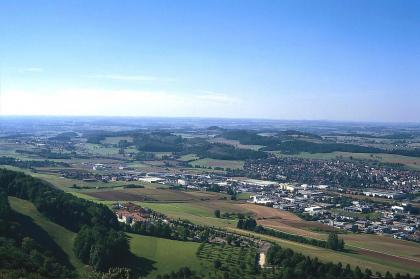 Blick von einem bewaldeten Hügel über eine besiedelte Landschaft. Neben Ackerflächen befinden sich auch einige Waldstücke zwischen den Siedlungen.