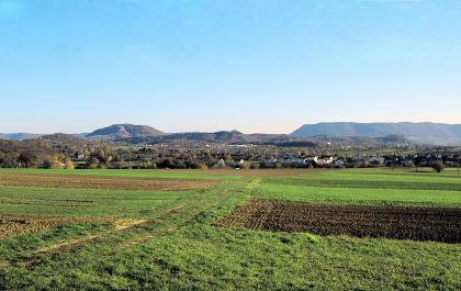 Blick auf flache Wiesen und Äcker. Im Hintergrund sind mehrere Siedlungen sowie verschiedene bewaldete Hügel und Berge zu erkennen.