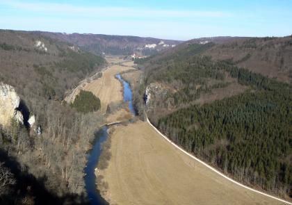 Aus großer Höhe blickt man auf ein schmales, hellbraunes Tal, durch das sich ein Fluss schlängelt. Links und rechts des Tales sowie im Hintergrund steigen bewaldete Hänge auf, teilweise durchsetzt mit blanken Felsen.