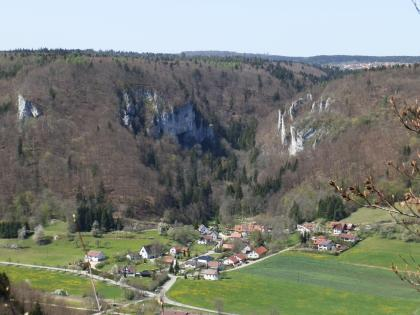 Aus großer Höhe blickt man auf eine in flacher Grünlandschaft angelegte Siedlung, hinter der sich zwei mächtige, bewaldete Höhenzüge auftürmen. Weißlich graue Felsspitzen unterbrechen die Bewaldung.