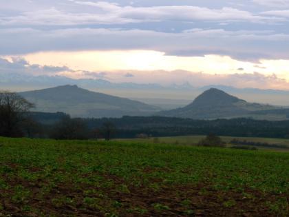 Über grüne Ackerflächen und einen breiten Waldstreifen im Mittelgrund geht der Blick auf zwei bewaldete, kegelförmige Erhebungen. Weit entfernt sind dahinter schneebedeckte Gebirgszüge erkennbar.