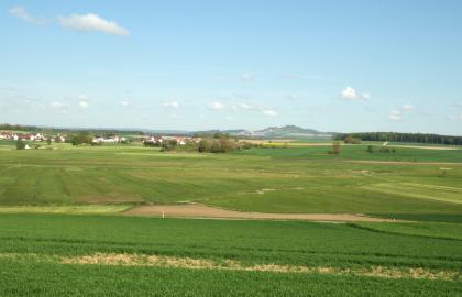 Blick über ein flachwelliges grünes Hügelland mit einer Siedlung links im Hintergrund und einem Waldstreifen rechts. Noch weiter hinten ist eine bergige Erhöhung erkennbar.