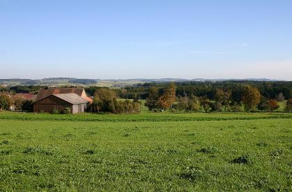 Blick auf leicht abfallendes Wiesenland mit einer Siedlung links und dichtem Wald im Mittelgrund. Im Hintergrund sind teilweise bewandelte Hügelrücken erkennbar.