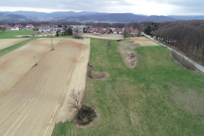 Blick aus der Luft auf ein begrüntes, die rechte Bildhälfte füllendes, und ein hellbraunes, die linke Bildhälfte füllendes, Feld. Dahinter befindet sich eine Siedlung. Am Horizont ist eine Bergkette zu sehen.