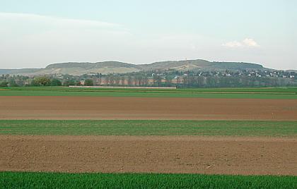Blick über teils kahle, teils bewachsene Ackerböden in waagrechter Ausrichtung. Im Hintergrund bewaldete Bergrücken.
