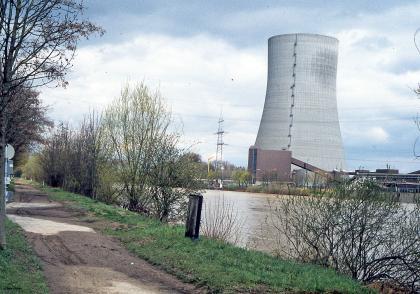 Das Bild zeigt einen Uferabschnitt des Neckars bei hohem Wasserstand. Am linken Ufer sind noch Spuren von Überflutung sichtbar. Am rechtsseitigen Ufer des Flusses steht der Kühlturm eines Kraftwerks.