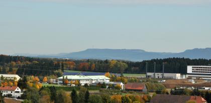 Von erhöhtem Standort blickt man auf abgestufte, bewaldete Berge. Vorgelagert sind ein Waldgürtel, der verschiedene Gebäude umschließt. Rechts ist eine Baugrube für Neubauten erkennbar.