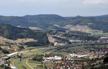 Blick aus großer Höhe auf eine breite Flussaue mit Siedlung. Die Aue wird zum Hintergrund hin von bewaldeten Bergen gesäumt. Etwa in der Bildmitte ist ein Steinbruch zu erkennen.