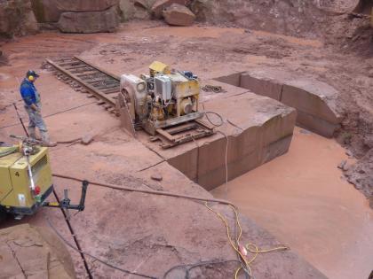 Blick von oben auf die rötlich graue Sohle eines Steinbruches. Eine auf Schienen gesetzte Maschine sägt Blöcke aus dem Gestein. Rechts ist das Gestein bereits lückenhaft.