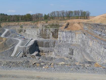 Blick von oben in einen Steinbruch. Zu erkennen ist der Boden sowie mittig und rechts terrassenförmig aufsteigende, hohe Gesteinswände. Links sind Fahrstraßen und Rohrleitungen angelegt. Im Hintergrund ist ein Streifen Wald.