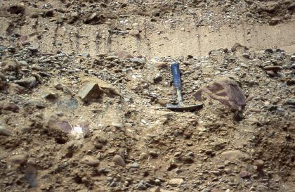 Das Bild zeigt hellbraunes Bodenmaterial, in das neben Kiesen auch größere Gesteinsbrocken eingebacken sind. Oben verläuft eine glattere Schicht, etwa so breit wie der darunter liegende Hammer.