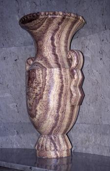 Blick auf ein steinernes Gefäß mit Sockel, trichterförmigen Öffnung oben und seitlichen Haltegriffen. Das Gestein ist gelblich bis rötlich mit dunklen, senkrecht verlaufenden Streifen.