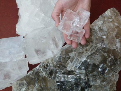 Brocken und Handstücke von Steinsalz in weiß (links) und grau (rechts).
