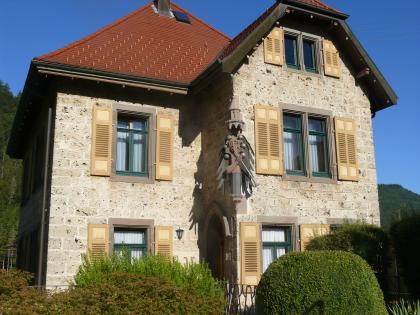 Blick auf ein zweistöckiges, links zurückgesetztes Gebäude aus hellgrauen Steinquadern. Das Gebäude hat grüne Fenster, braune Steinrahmen und hellbraune Fensterläden. Das zweiteilige Dach ist erhöht. Am vorgesetzten Hausteil rechts ist eine Skulptur.