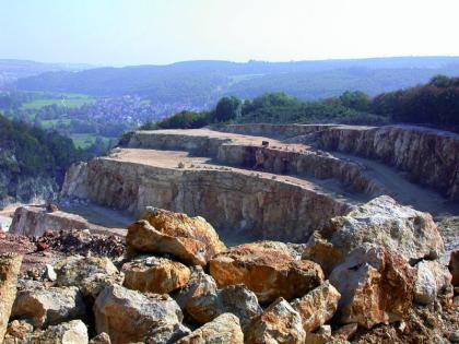 Blick von oben über rotbraune und graue Steinblöcke auf die Sohlen eines Steinbruches. Die oberste Sohle verjüngt sich links zu einer Auffahrtsrampe. Die zweite Sohle ist erheblich niedriger als die darunterliegenden. Im Hintergrund Wald und Berge.