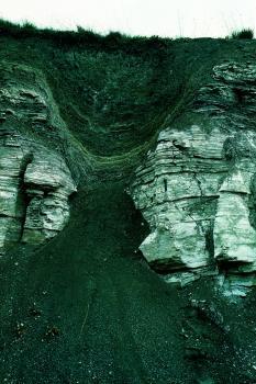 Das Bild zeigt eine gräuliche, unebene Felswand. Am oberen Rand, unterhalb der Grasnarbe, ist die Felswand trichterförmig eingesackt.