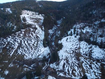 Blick aus der Vogelperspektive auf einen teilweise schneebedeckten Hang, der vor allem am oberen Ende bewaldet ist. Im Zentrum des Bildes ist ein Bach zu erkennen, der stark angeschwollen den Hang hinabfließt.