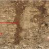 Zu sehen ist eine Wand, an der hellbraunes Gestein zu Tage tritt. Zwischen den Gesteinen befindet sich eine Spalte, die mit dunkelbraunem Material verfüllt ist. Links stehen Infos zur Böschung.