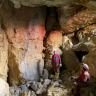 Das Bild zeigt zwei Personen in Schutzanzügen und mit Helm, die in einer Höhle stehen. Sie sind umgeben von hellbraunem bis gelblichem Gestein.
